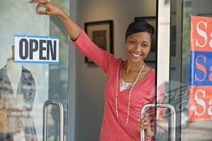 African business owner hanging open sign on shop door